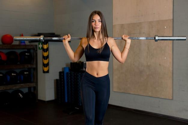 Sexy sportlerin mit einer schönen figur steht im fitnessstudio und hält eine langhantel.