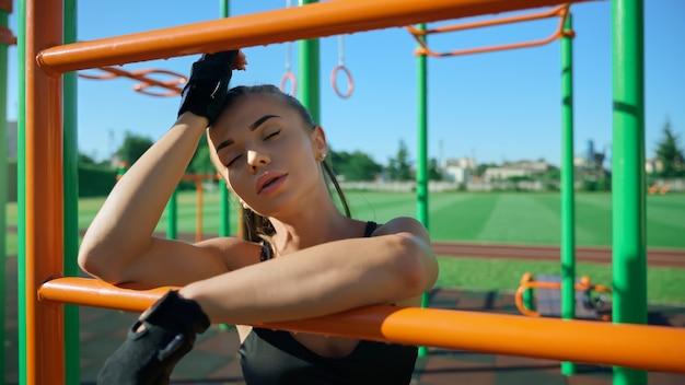 Sexy sportlerin posiert am sportplatz