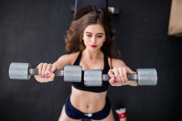 Sexy sportliche muskulöse junge frau, die mit zwei metallischen hanteln ausarbeitet