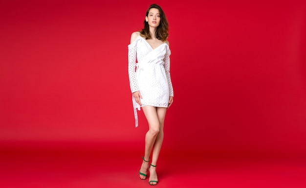 Sexy stilvolle frau im sommermode-trend weißes kleid, das auf rotem studio aufwirft