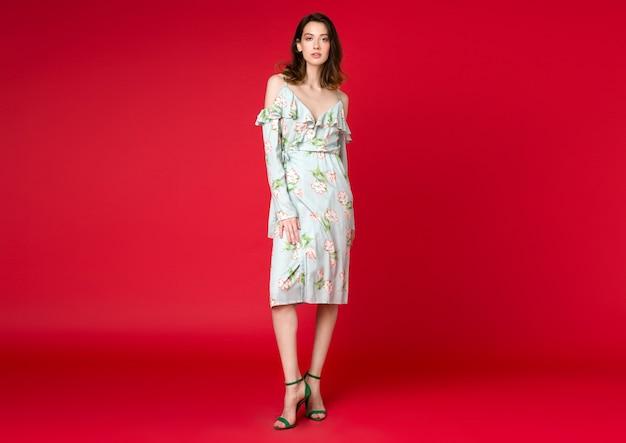 Sexy stilvolle frau im sommermode-trendkleid, das auf rotem studio aufwirft