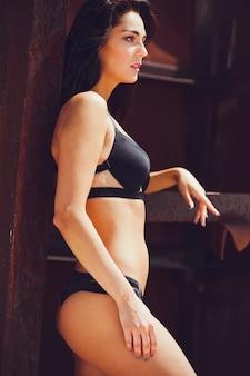 Sexy strand-fotoshooting der mode-mode-art der jungen schönen frau im hellen bikini-badeanzug im sonnenuntergangslicht im urlaub. blauer meerschaum und weißer sand