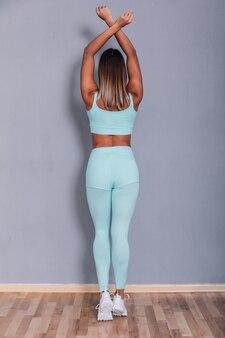 Sexy süßes lockiges blondes mädchen mit schöner haut, das im studio aufwirft. tragendes stilvolles blaues sommerkostüm, stilvolles lederoberteil. rückansichtsbild.