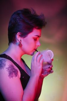 Sexy tätowierungsfrau, die ein rauchgeistgetränk trinkt
