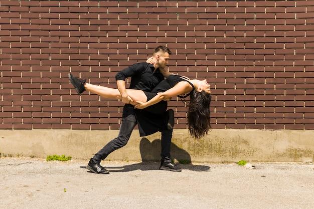 Sexy tangotänzer, der gegen wand tanzt