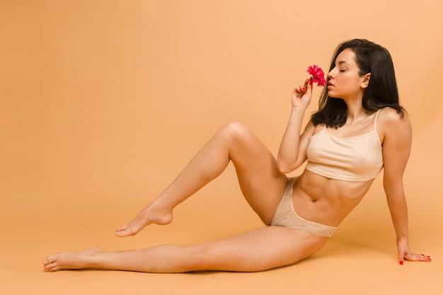 Sexy und schöne frau in unterwäsche, die blume riecht. schönes und gesundes mädchen mit jungem und fittem körper, der in unterwäsche posiert. sport, fitness, ernährung, ernährung und gesundheitskonzept.