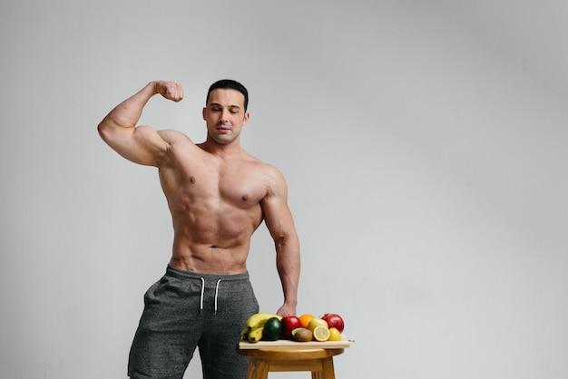 Sexy veganer kerl mit einem nackten torso, der neben obst aufwirft. diät. gesunde ernährung