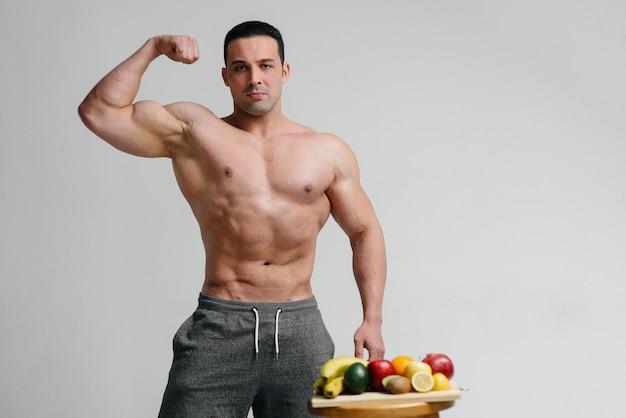 Sexy veganer typ mit nacktem oberkörper posiert im studio neben obst. diät. gesunde ernährung