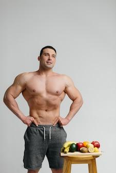 Sexy veganer typ mit nacktem oberkörper posiert im studio neben obst. diät. gesunde ernährung.