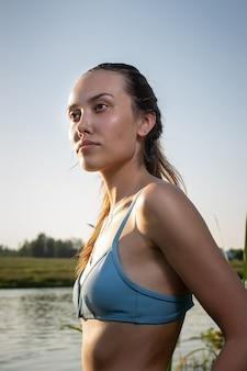 Sexy verführerische junge dünne frau im blauen bikini steht im see bereit zum schwimmen
