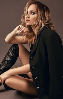 Sexy verlockendes blondes mädchen in der unterwäsche und im schwarzen mantel