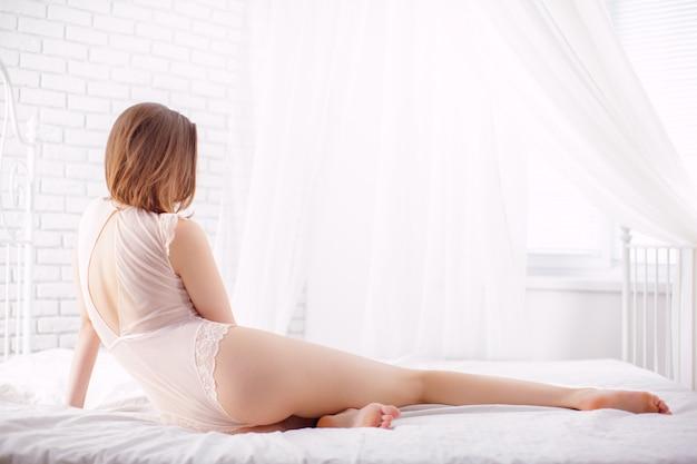 Sexy vorbildliches lügen der jungen frau auf bett