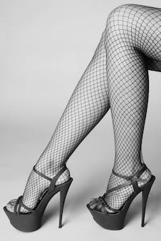 Sexy weibliche beine in roten striptease-schuhen mit hohen absätzen und netzstrümpfen