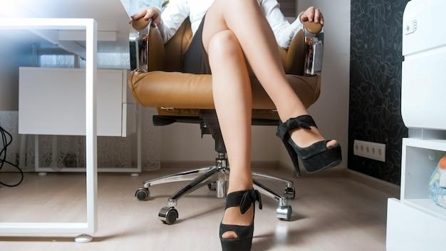 Sexy weibliche füße in schuhen mit hohen absätzen, die im ledersessel im büro sitzen.