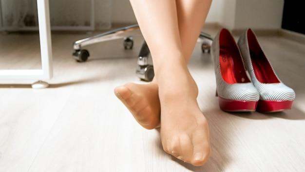 Sexy weibliche füße in strumpfhosen oder strümpfen unter dem bürotisch.