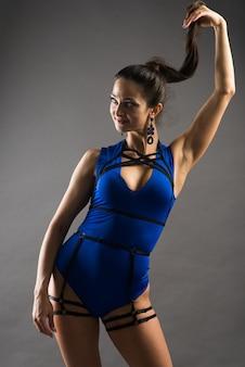 Sexy weibliche stangentänzerin, die blauen bodysuit und hohe absätze auf einem grauen hintergrund trägt