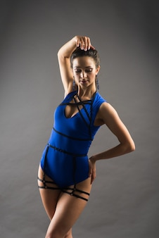 Sexy weibliche stangentänzerin mit blauem body und hohen absätzen auf grauem hintergrund