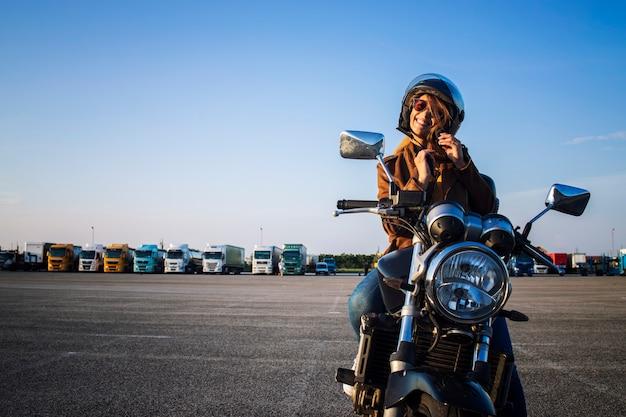 Sexy weiblicher motorradfahrer, der auf retro-artmotorrad sitzt und helmgürtel vor fahrt festhält