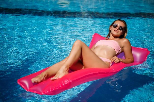Sexy weibliches modell, das auf einer matratze im pool ausruht und ein sonnenbad nimmt. frau in einem rosa bikini-badeanzug, der auf einer aufblasbaren rosa matratze schwimmt. spf und sonnencreme