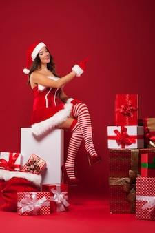 Sexy weihnachtsmann mit vielen weihnachtsgeschenken, die auf roten kopienraum zeigen