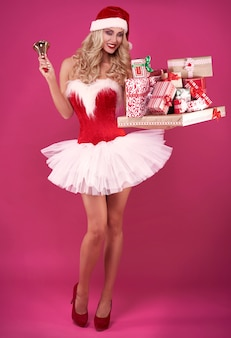 Sexy weihnachtsmann mit weihnachtsgeschenken und glocke