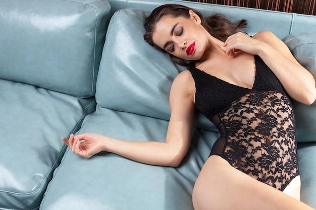 Sexy weiße brünette frau in spitzenwäsche, die auf ledersofa innen entspannt