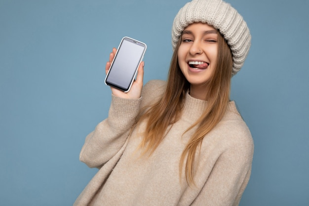 Sexy zwinkernde schöne junge frau mit stylischem beige pullover und beige gestrickter wintermütze winter