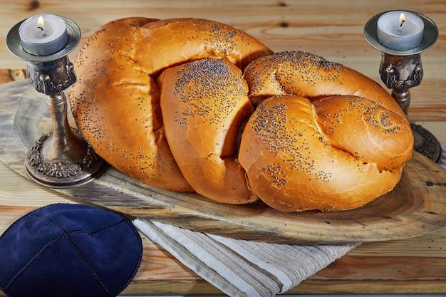 Shabbat challah auf einem holzständer mit kerzen und einem rustikalen ballen. shabbat shalom