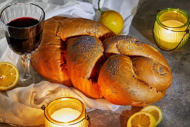 Shabbat challah mit einer weißen serviette, mit kerzen, einem glas wein und rustikalen zitronen. shabbat shalom