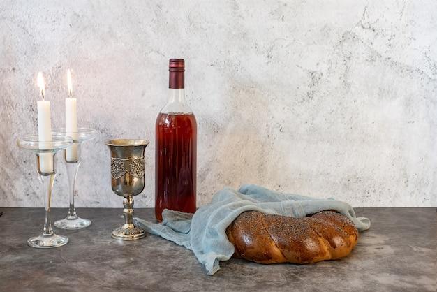 Shabbat shalom - challa-brot, shabbat-wein und kerzen auf grauem hintergrund. seitenansicht. mit kopierplatz