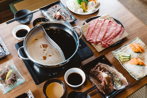 Shabu-set mit seltenen scheiben wagyu a5, shabu shoyu und klarer basis, lachs, sushi.