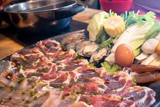 Shabu-shabu-servierplatte auf tabelle am japanischen restaurant mit dem leuteessen