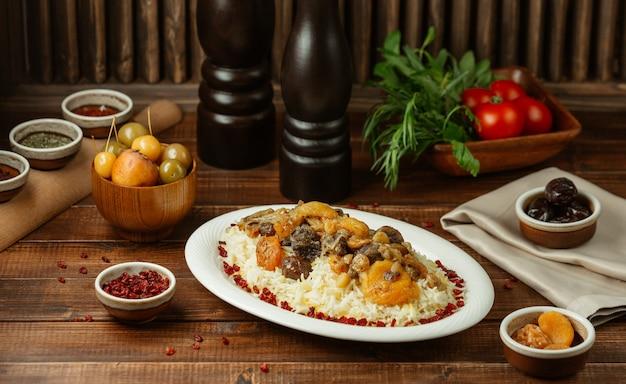 Shah plov, reis mit saisonalen und trockenen früchten garnieren