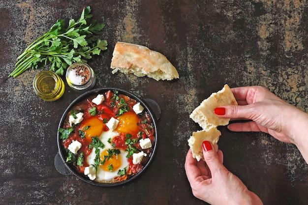 Shakshuka mit fladenbrot. nahöstliche küche. arabisches, israelisches, marokkanisches frühstück oder mittagessen. spiegeleier in tomaten-gemüse-sauce mit gewürzen und kräutern.