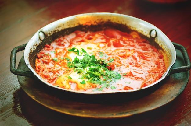 Shakshuka. traditionelles jüdisches essen und rezept aus dem nahen osten. spiegeleier, tomaten, paprika und petersilie in einer pfanne.