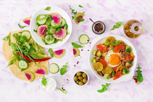 Shakshuka und frische salatgurke, wassermelonenrettich und rucola