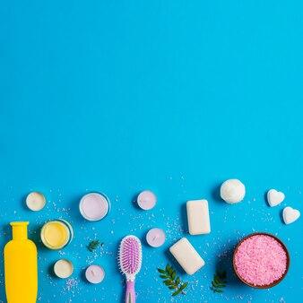 Shampoo-flasche; sahne; seife; badebombe mit rosa salz auf blauem hintergrund