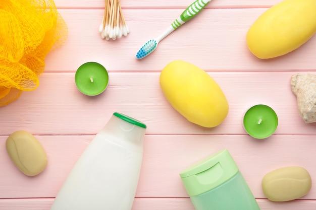 Shampoo, seife, aromakerzen und andere toilettenartikel. frühlingszusammensetzung auf rosa wand