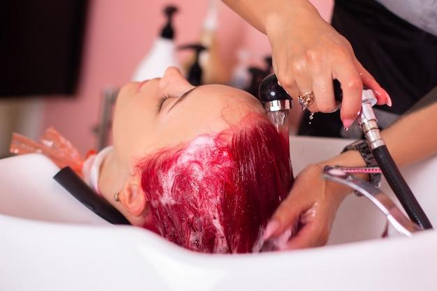 Shampoo waschen des weiblichen kopfes mit langen rosa haaren