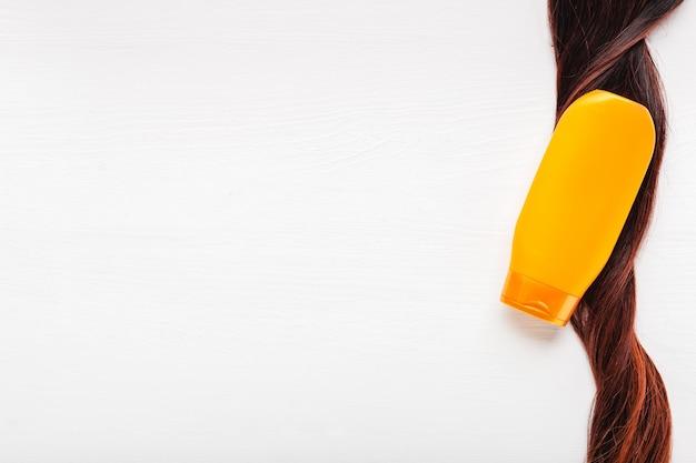 Shampooflasche auf lockenstrang-haarlocke auf weißem hintergrund. orangenflasche shampoo kopierraum.