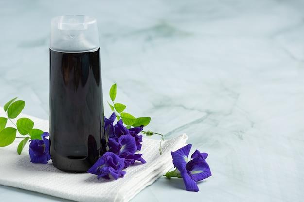 Shampooflasche der schmetterlingserbsenblume legte auf weißen marmorhintergrund