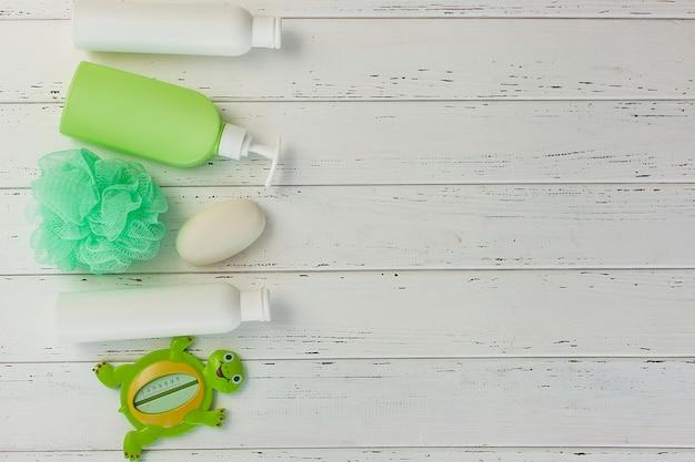 Shampooflaschen auf hölzernem backround. babywanne zubehör. kindertoilettenzeug. badewannen, balsam, meersalz, seife.