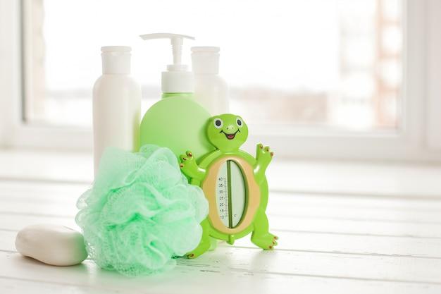 Shampooflaschen auf holztisch. babywanne zubehör. kindertoilettenzeug. badewannen, balsam, meersalz, seife.