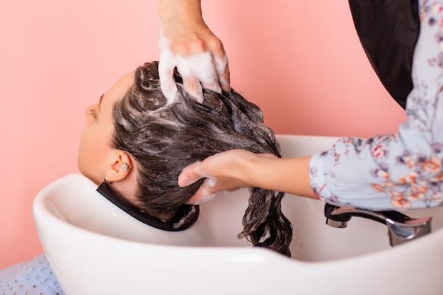 Shampoowäsche von brünetten haaren von frauen