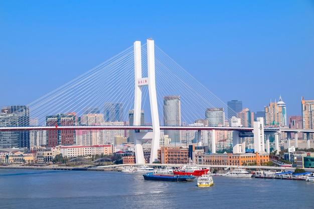 Shanghai, china - 18. februar 2021: die nanpu-brücke ist die erste brücke, die den huangpu-fluss vom zentrum shanghais aus überquert und ihn mit dem bezirk pudong auf der anderen seite des flusses verbindet.