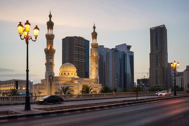 Sharjah. abend al qasba moschee im städtischen straßenbild.