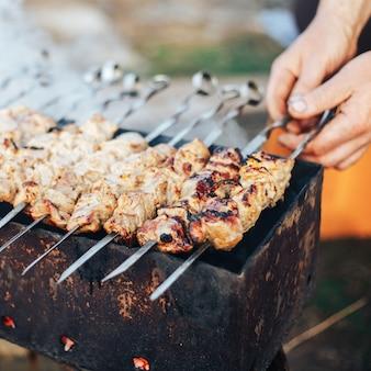 Shashlyk bereitet sich im freien vor, die hände des mannes, die kebab, russisches fleisch im garten coocking sind