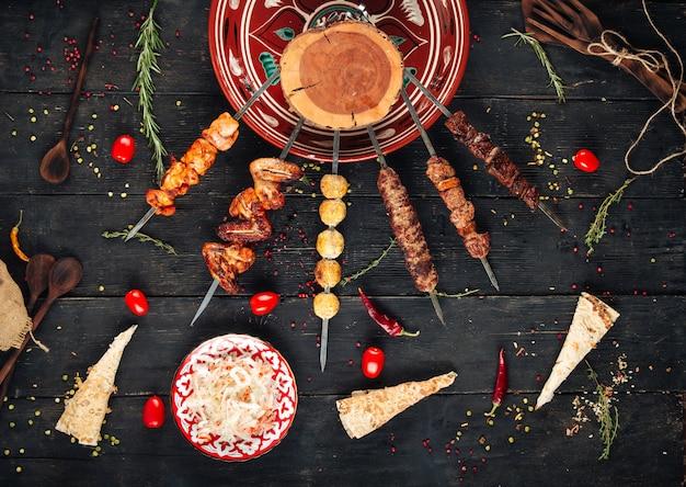 Shashlyk spießt kebabs auf dem dunklen holztisch auf