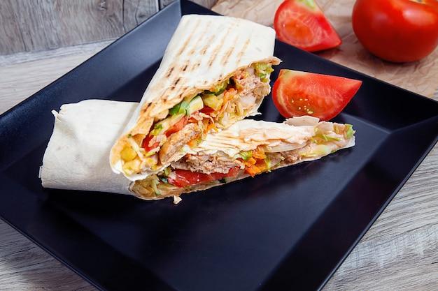Shaurma, shawerma, kebab, serviert auf einem dunklen teller mit sauce. veganes essen mit falafel. arabische oder östliche küche. kopierraum, selektiver fokus. geschnittene shaurma mit gewürzen, kirschtomaten und paprika