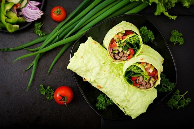 Shawarma aus saftigem rindfleisch, salat, tomaten, paprika und zwiebel im fladenbrot